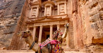 Spectacular view of two beautiful camels in front of Al Khazneh (The Treasury) at Petra. Petra is a historical and archaeological city in southern Jordan.